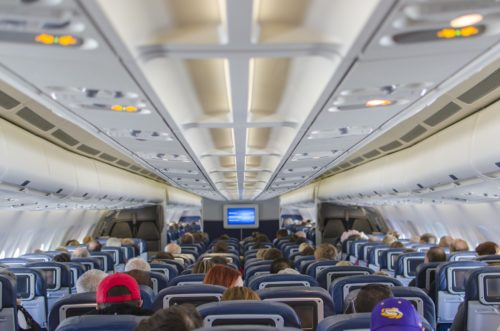 Image of people on an airplane that could use some noise cancelling headphones