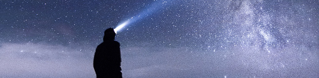 man looking at the stars with a rechargeable headlamp on his head