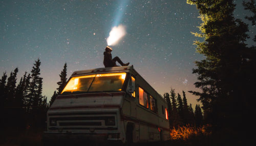 Person sitting on top of an RV looking up with a rechargeable headlamp