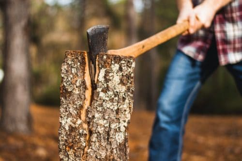 camping axe being used to split a log