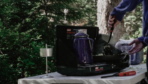 Person using a folding camping table to cook with a gas camp stove.