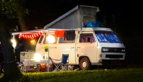 Cozy van with lights and an awning out being powered by a camping generator