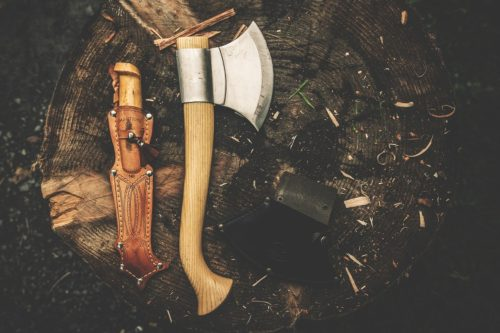 Small survival hatchet and knive laying on a stump