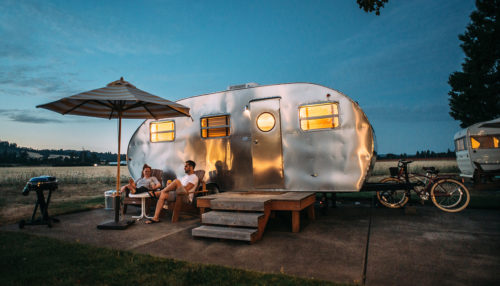 Old aluminum travel trailer with people sitting outside