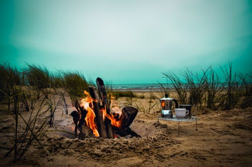 Small folding camping table on a beach next to a campfire.