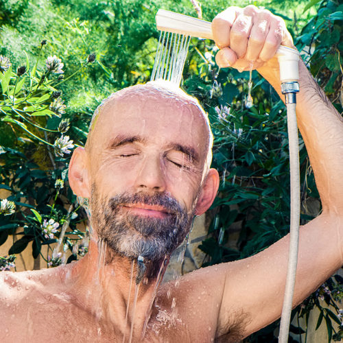 man using a shower head to take a shower outside