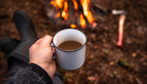 Coffee made with an RV coffee maker by a campfire.