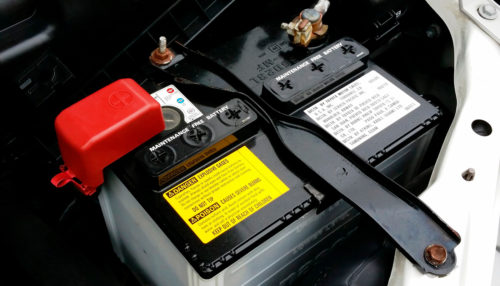 Car battery connected to a deep cycle battery charger