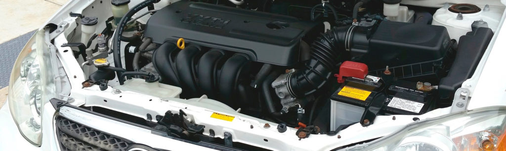 engine and battery under the hood of a car