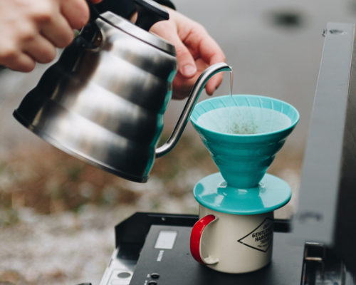 Pouring water into a non-electric coffee maker using a gooseneck kettle.