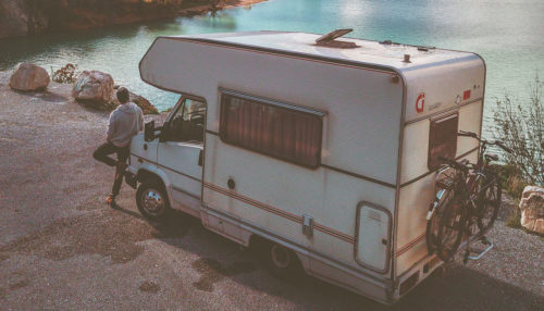Hitch RV bike rack on the back of a camper by a lake