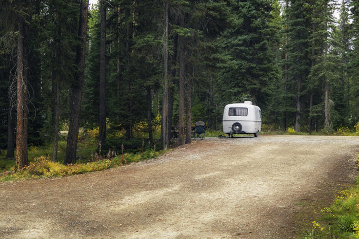 Trailer standing in a dry campground that's perfect for using an RV portable waste tank in.