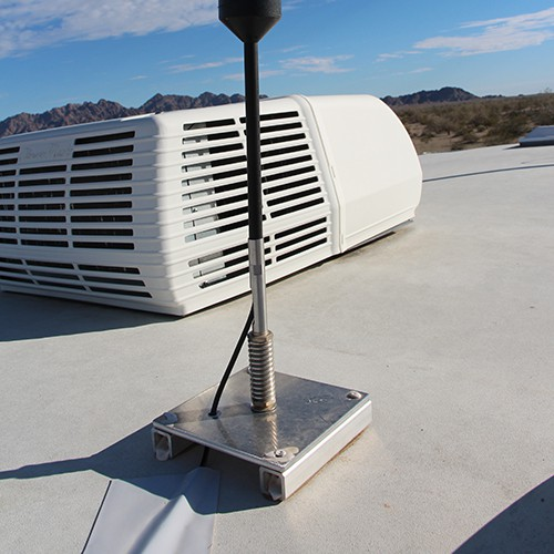 Cell phone booster antenna mounted to the roof of an RV