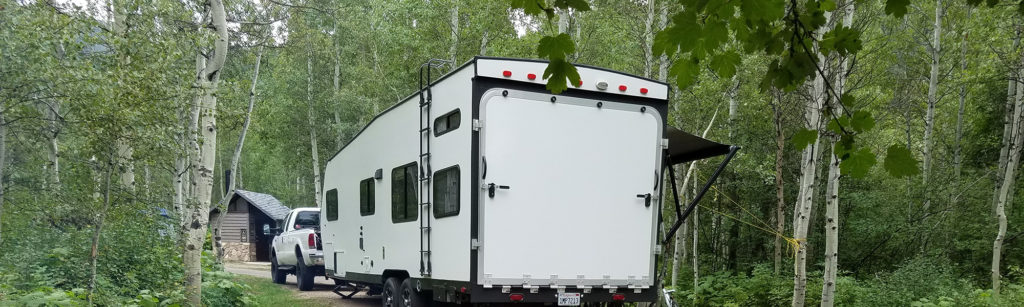 Toy hauler travel trailer with a remote start generator onboard