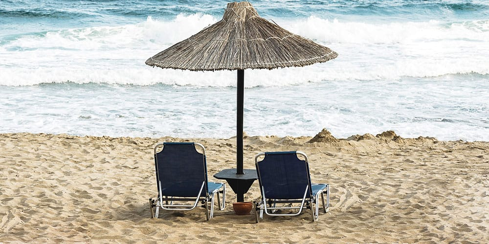 Folding beach lounge chairs sitting side by side on a beach.