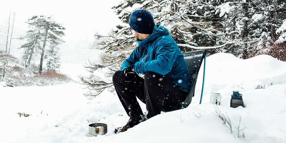 Man sitting in a collapsible lightweight backpacking chair in the snow.