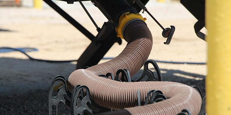 Camco Sidewinder sewer hose support holding up the sewer hose for an RV