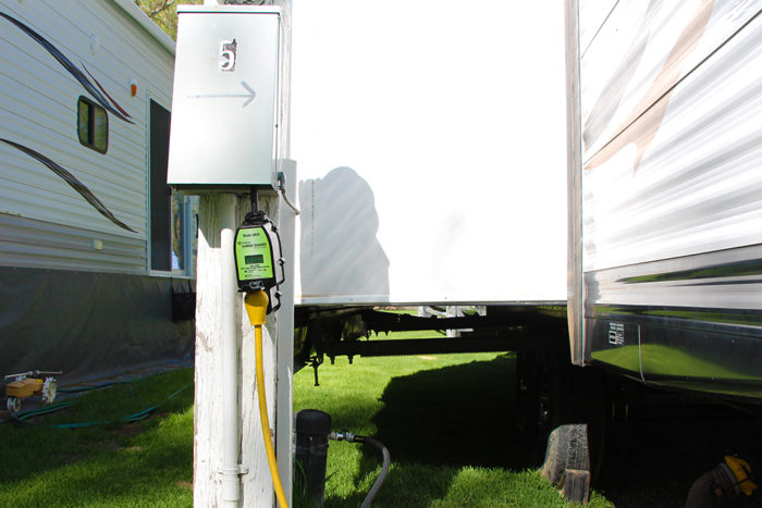 RV surge protector and EMS plugged into a power pedestal at an RV park