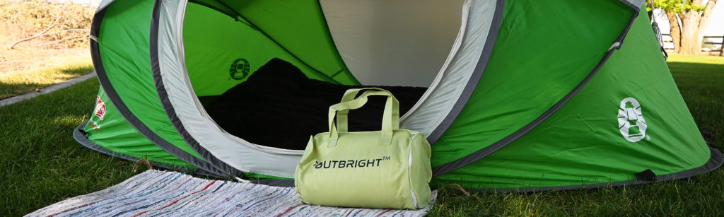Outbright memory foam pillow sitting next to a tent at a campsite