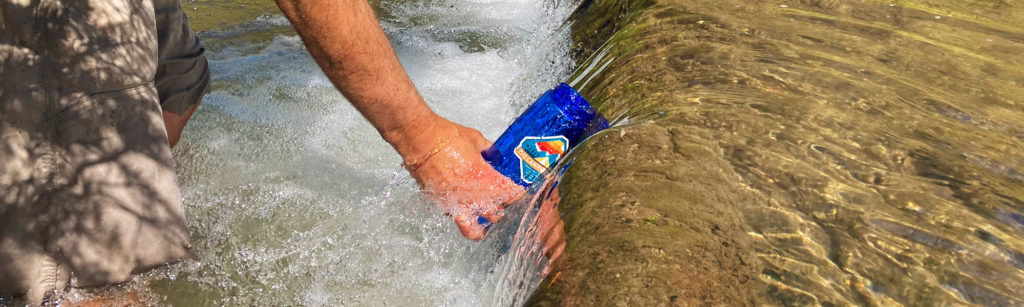 Simpure Water Bottle Filter being filled from a small mountain stream