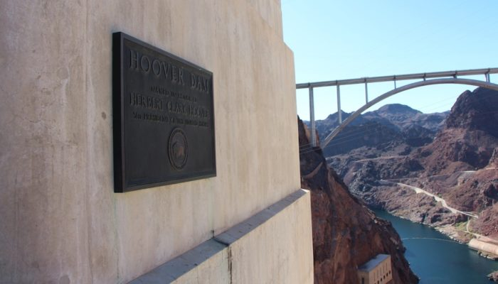 Sign on Hoover Dam with the Mike O'Callaghan–Pat Tillman Memorial Bridge in the background.