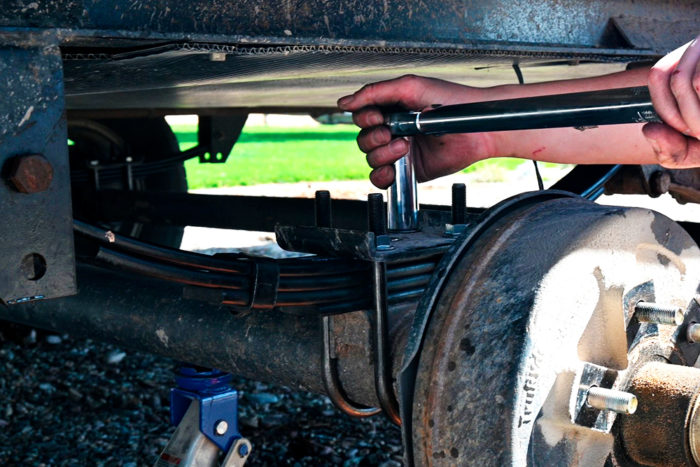 Loosen the U-bolt nuts before removing the shackle bolts that hold up the leaf springs.