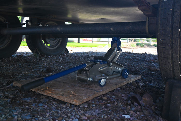 Place a floor jack and block of wood or a jack stand under the axle before you start removing the leaf spring