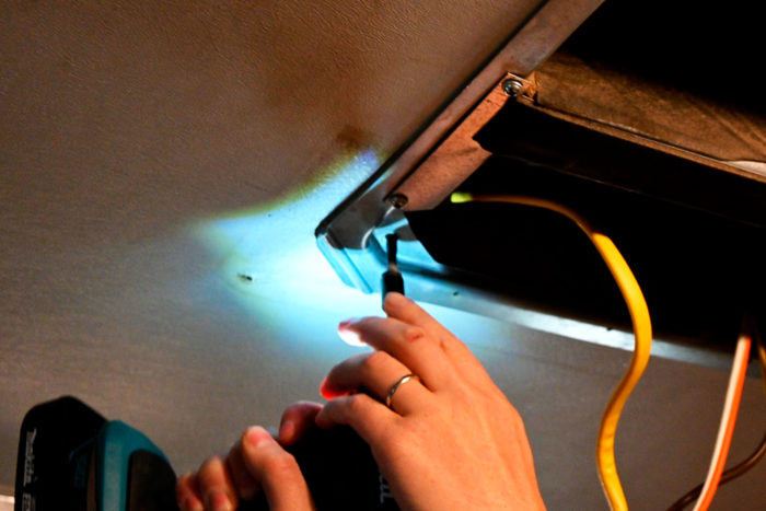 Removing the main bolts on an RV AC that will be replaced with a 12V fan.