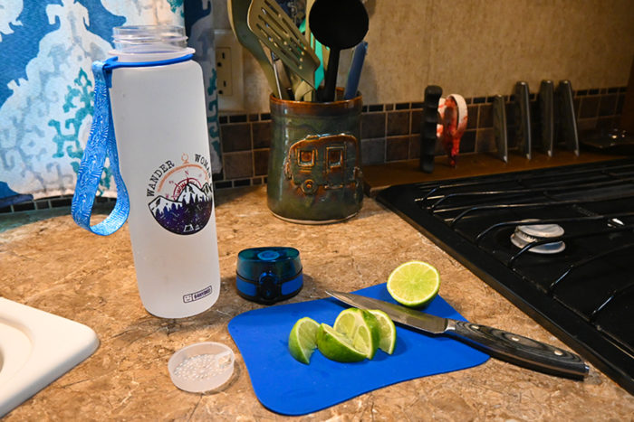 64Hydro water tracker bottle next to some limes