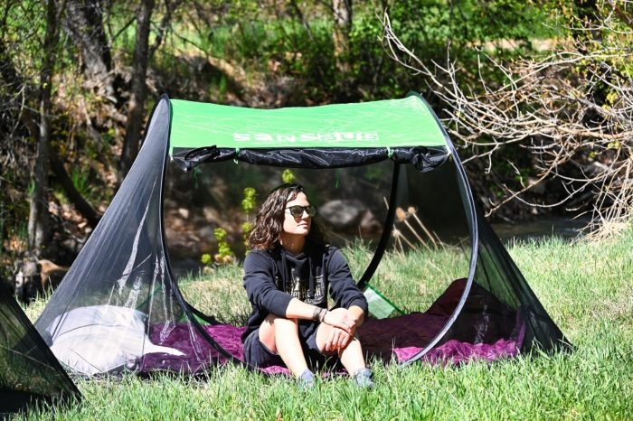 Person sitting in the Sansbug 3 person popup screen tent