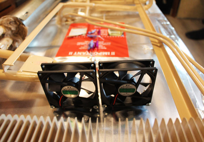 Two 12V fans on the back of an RV fridge to help airflow to make the fridge more efficient
