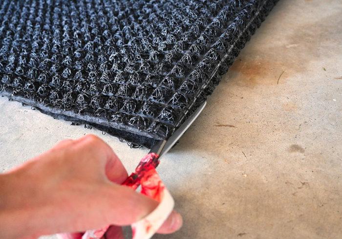 Den-Dry mattress underlay being cut in half with scissors
